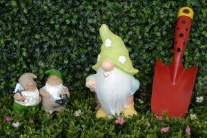 A picture of 3 garden gnomes and a red spade
